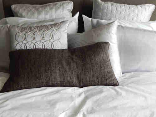 Différents oreillers synthétiques et naturelles sur lit