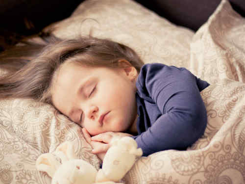 Enfant dort sur un oreiller de petite taille