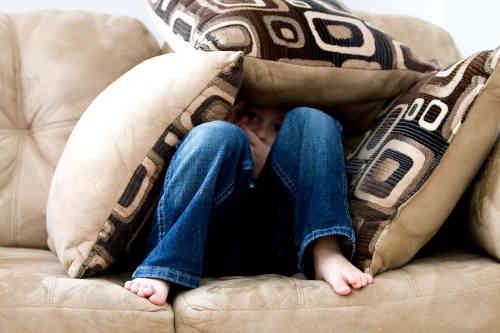 Enfant sur un canapé et des oreillers